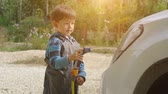 working parents : Little boy washing white car in the garden. Summer Stock Footage