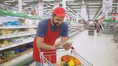 gündelik : supermarket employee leaning on the shopping cart and using mobile apps on his tablet Stok Video