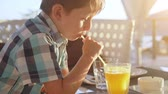 casual clothing : Cute little boy drinking fresh orange juice from glass in city cafe