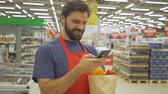 assistent : Smiling supermarket employee using mobile phone and holding shopping bag in supermarket