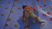corajoso : Activity of rock-climbing on artificial climbing walls, Caucasian boy in a harness climbing a wall with grips