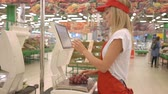 verkoopster : Female staff in red uniform weighing grape on electronic scales with touch screen in supermarket