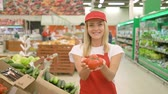 caps : Young female sales clerk smiling and holding fresh tomatoes at supermarket.