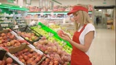 assistent : Beautiful supermarket saleswoman in red uniform giving thumb up Stockvideo