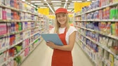 verkoopster : Female supermarket employee in red uniform holding a clipboard in front of shelf in supermarket
