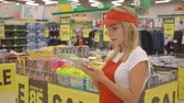 assistent : Female supermarket clerk using apps on a digital tablet, innovative technology and work concept,