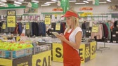 assistent : Female merchandiser in red uniform checking products with digital tablet