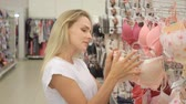 bh : Beautiful young woman selecting new bra in lingerie department
