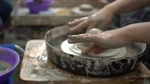 ceramic : Young potter trying to make a cup on pottery wheel in a workshop.