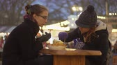 batatas fritas : Beautiful sisters eating fried chips in cafe at Christmas market Winter market Stock Footage