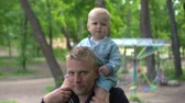 first : Young man gives little baby boy a ride on shoulders in park Slow motion Stock Footage
