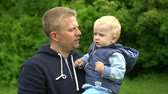 hrdý : Young happy father holds little son on hands and plays in park