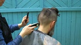 ustalık : Close up of mens haircut with electric razor clipper in open air barbershop Hairstyling process