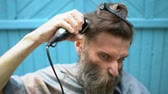 man grooming : Strange hipster man with big gray-haired beard and ridiculous grimace trying to cut own hair with electric razor clipper Stock Footage