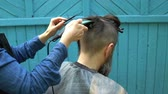 trimmer : Female hairdresser making male haircut with hair electric razor and comb in hairdressing salon on open air