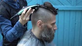 мастерство : Woman hairdresser making hipster male haircut for middle aged man with hair electric razor and comb in outdoor hairdressing salon