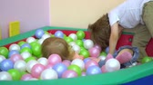 kreş : Laughing cute blonde caucasian preschool toddler playing in multi coloured ball pool. Kindergarten