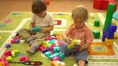 rozmanitý : Happy preschool kids playing with multi coloured blocks at indoor playground. Education in nursery school