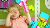 Top view of cute child playing with multi coloured building blocks in preschool Child development in kindergarten
