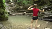 Young woman makes video on action camera in mountain forest on the river
