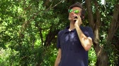 Attractive emotional mature man with beard and sunglasses talks by smartphone in the forest or park Wideo