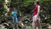 Women makes photos by smartphone in mountain tropical forest with large stones