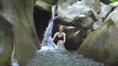 pedregulhos : �ttractive girl in slow motion splashing clear water of mountain lake and looks to camera with small waterfall in green tropical forest with boulders and moss on background in jungle natural park