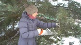 alasca : Attractive caucasian woman cutting pine branches by saw in her winter snowy garden for Merry Christmas and Happy New Year Vídeos