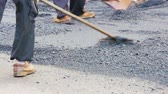 ускорять : Road construction workers put up a hot asphalt on a street. Small steamroller.