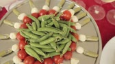 topped : On a large tray canapes from tomatoes, mozzarella and sauce , in the center of the tray pea pods