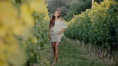 inclinar : Shy girl goes along the grape rows Stock Footage