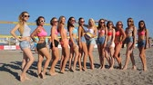 A group of young attractive girls with ball posing for photo, smiling and waving their hands at the beach Vídeos