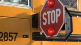 образование : Two takes of the stop sign on a school bus swinging out to signal drivers to stop for school children.