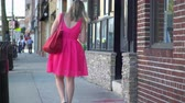 astarlı : A view of a woman in a bright pink dress walking down a sidewalk