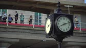 condutor : Clock in foreground with commuters waiting on a train station platform behind it