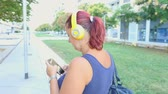 earbuds : smiling woman walking listen music with headphone Stock Footage
