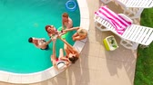 Aerial flight : Happy group of young friends hanging out together by the pool with drinks