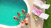 uvedení : Aerial flight : Happy group of young friends hanging out together by the pool with drinks