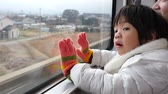 ferrovia : Happy asian child looking out train window outside