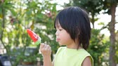 фрукты : Cute Asian child eating an ice cream outdoors