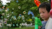 pistola : Cute Asian child Shooting Bubbles from Bubble Gun,slow motion