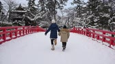 Asian children holding hand and running together on red bridge,Hirosaki castle,Japan