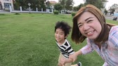 Asian mother and her son using a Action camera taking picture in the park
