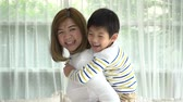 proteger : Asian child on a piggy back ride with his mother at home slow motion Vídeos