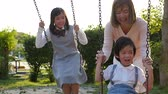 jardim de infância : Asian family having fun on swing together in the park slow motion