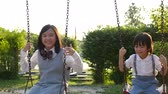 jardim de infância : Asian girl and her brother playing swing together in the park slow motion
