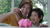 świnia : Cute Asian child putting a coin into a piggy bank slow motion