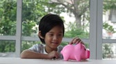 świnia : Cute Asian child putting a coin in to a piggy bank slow motion Wideo