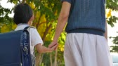 grade : Asian mother holding hand of little son with backpack outdoors, back to school slow motion Stock Footage
