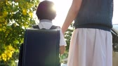 notas : Asian mother holding hand of little son with backpack outdoors, back to school slow motion Vídeos